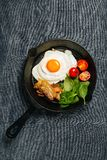 Top view of tasty bacon, egg, spinach and tomatoes with fry pan on grey linen cloth royalty free stock photos