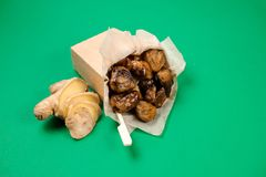 Top view of tasty chestnuts with sauce and fresh ginger on green background Stock Images