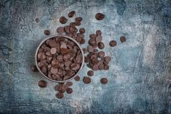 Top view of dark chocolate drops or morsels in bowl on blue concrete background
