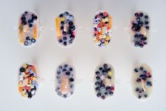 Top view of tasty homemade popsicles with organic fruits and berries. On grey royalty free stock photography