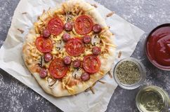 Top view of tasty hot pizza with mashrooms,cheese,tomatoes, sauce and delicious slices of sausages. Top view of homemade vegetarian pizza, traditional kind of stock images