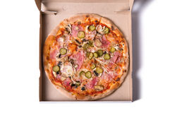 Top view of tasty Italian pizza with ham, cucumber, and onion in Stock Image