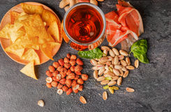 Top view of tasty snacks and dark beer on a table background. Peanuts, pistachios, prosciutto with a glass of beer. Cold. A view from above on different tasteful Stock Photography