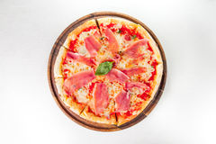 Top view Tasty whole Italian pizza topped with thinly sliced prosciutto ham on the served restaurant table. Selective focus Stock Photo