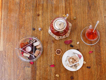 Top view of tea and cookies. Scented candle and a cup of red tea on a wooden background. Fancy kettle with fruit tea. Royalty Free Stock Photos