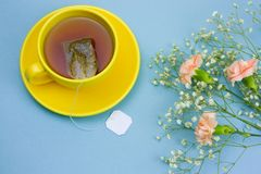 Tea cup with tea bag and bouquet of flowers. Top view tea cup with tea bag and bouquet of flowers royalty free stock images