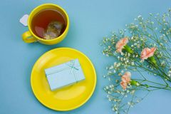 Tea cup with tea bag,gift box on a plate and bouquet of flowers on a pastel blue background. Top view tea cup with tea bag,gift box on a plate and bouquet of stock photos