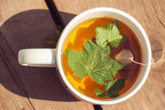 Top view of tea with currant leaf in white cup.  Stock Photo