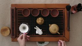 Top view tea set a wooden table for tea ceremony background. The girl pours boiling water into a teapot.  stock video footage