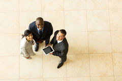 Top view team. Top view of cheerful business team using tablet computer Royalty Free Stock Photography