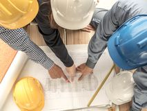 Top view teamwork concept, Engineer and workers discussing project of new building. ,Team of architects Asian people in group on. Construction site check royalty free stock photography