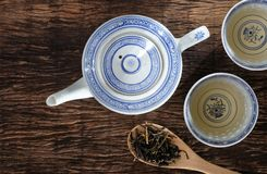 Tea pot and dry tea leaf. Top view of teapot and dry tea leaf on wooden table top stock photos
