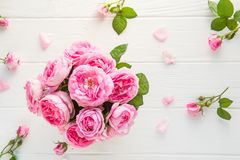 Top view tender pink tea roses bouquet on the rustic white wooden table with petals. Floral background. Greeting postcard mock up. Summer, spring flowers. Flat stock photos