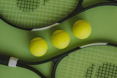 Three tennis balls and two tennis rackets on green background. Top view of tennis conceptual objects set on green color surface Stock Photos