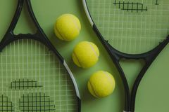 Three tennis balls and two tennis rackets on green background. Top view of tennis conceptual objects set on green color surface Royalty Free Stock Images