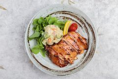 Top view of Teriyaki chicken served with potato salad, sliced lemon, totmato and green oak in round stone plate on washi. Royalty Free Stock Photos