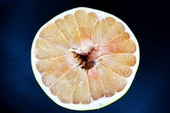 Textured ripe slice of pomelo citrus fruit on the dark background. close up. royalty free stock images