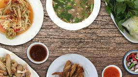 Top view Thai food ,papaya salad. `Som Tum`,grilled chicken,vegetables,pork spare rib spicy soup,sweet chili sauce,spicy pork noodle on wooden background,copy stock photography