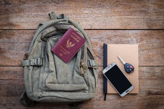 Top view Thailand passport, backpack, smartphone, car key and bo. Ok on wood plank background Stock Photos