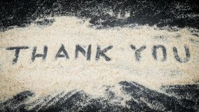 Top view of Thank You text written on white sand