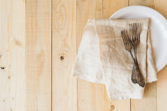 Top view three antique forks and napkin on white plate Royalty Free Stock Images