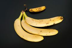 Top view of three big bananas and one mini banana isolated on black background royalty free stock photography