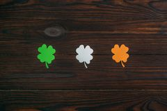 Top view of three clovers in colors of irish flag. On wooden table stock photos