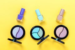 Three colorful Eye shadows pallets and Nail polishes on yellow background. stock photos