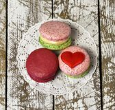 Top view of three delicious macarons and love heart symbol on napkin on wooden table. royalty free stock images