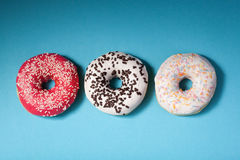 Top view of three donuts isolated on blue background Stock Images