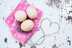 Top view of three eggs on rose napkin Stock Images