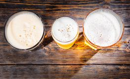Top view of three glasses with light, unfiltered and dark beer o Stock Images