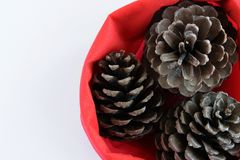 Top view of three pine cones in red bag, seasonal holiday background/concept. White background with space for text stock photography