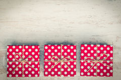 Top view of three red dotted gift boxes over white wood background. Copy space. Vintage effect. Royalty Free Stock Images
