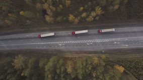 Top view three truck cars with freight container driving on suburban road. On background autumn forest. Freight truck cars moving on highway stock footage