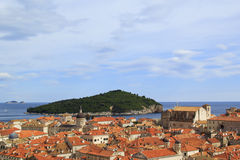 Top view of the  tile roofs and the sea in the Italian style in Dubrovnik, Croatia. Top view of the orange tile roofs and the sea in the Italian style in Royalty Free Stock Images
