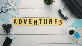 Top view time lapse hands laying on white desk word `ADVENTURES` decorated with travel items stock footage