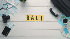Top view time lapse hands laying on white desk word `BALI` decorated with travel items stock video