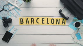 Top view time lapse hands laying on white desk word `BARCELONA` decorated with travel items stock footage