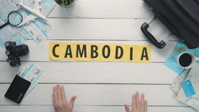 Top view time lapse hands laying on white desk word `CAMBODIA` decorated with travel items stock footage