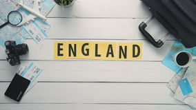 Top view time lapse hands laying on white desk word `ENGLAND` decorated with travel items stock video footage