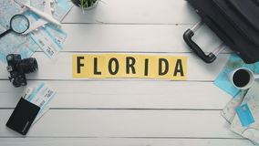 Top view time lapse hands laying on white desk word `FLORIDA` decorated with travel items stock video footage