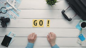 Top view time lapse hands laying on white desk word `GO` decorated with travel items stock footage