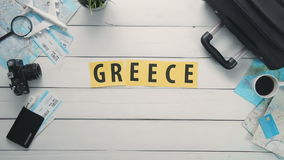 Top view time lapse hands laying on white desk word `GREECE` decorated with travel items stock video footage