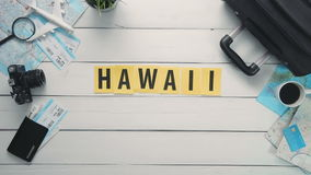 Top view time lapse hands laying on white desk word `HAWAII` decorated with travel items stock video