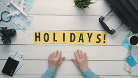 Top view time lapse hands laying on white desk word `HOLIDAYS` decorated with travel items. Travelling concept Top view time lapse hands laying on white desk stock video