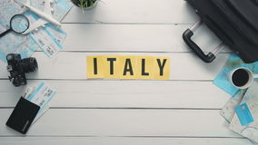 Top view time lapse hands laying on white desk word `ITALY` decorated with travel items stock video