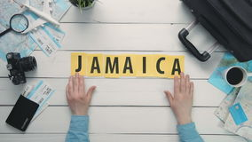 Top view time lapse hands laying on white desk word `JAMAICA` decorated with travel items. Travelling concept Top view time lapse hands laying on white desk word stock video