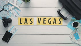 Top view time lapse hands laying on white desk word `LAS VEGAS` decorated with travel items stock video