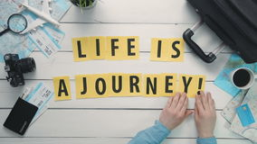 Top view time lapse hands laying on white desk word `LIFE IS A JOURNEY` decorated with travel items stock footage